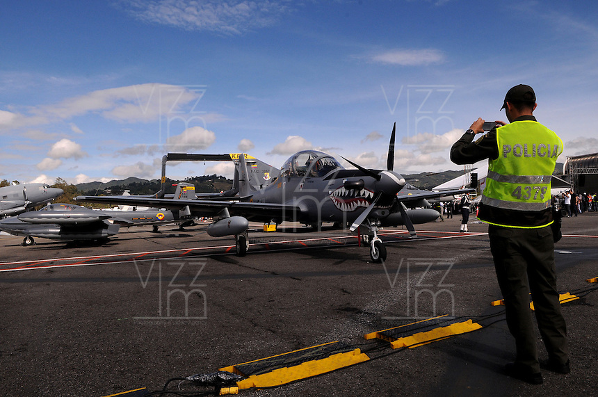 RIONEGRO - COLOMBIA - 11-07-2013: Un miembro de la Policia Nacional, toma una foto a un avión Super Tucano, en el aeropuerto de Rionegro, julio 11 de 2013. Se realiza en el Aeropueto Rionegro la F Air Colombia 2013, que se ha constituido como una de las exposiciones más representativas de la aviación en Latinoamérica. (Foto: VizzorImage / Luis Rios / Str.) A member of the Colombian Police, takes a picture of Super Tucano aircraft at the airport in Rionegro, July 11, 2013. It takes place in the Rionegro airport the F Air Colombia 2013, which has become one of the most representative exhibitions of aviation in Latin America. (Photo: VizzorImage / Luis Rios / Str)