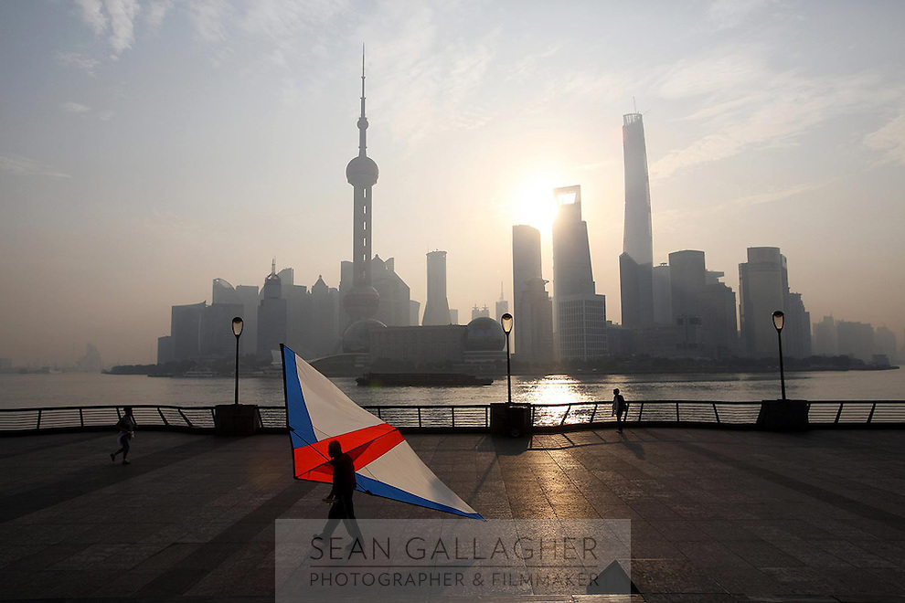 A man carries a large kite kite at sunrise in front of the distinctive Pudong skyline, 2014.<br />