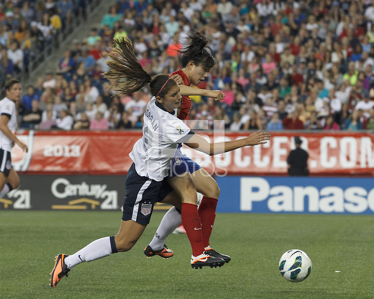 USWNT forward Alex Morgan (13) goes down in the penalty area for a penalty kick as Korea Republic defender Shim Seoyeon (4) defends. In an international friendly, the U.S. Women's National Team (USWNT) (white/blue) defeated Korea Republic (South Korea) (red/blue), 4-1, at Gillette Stadium on June 15, 2013.