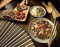 A stir fry meal scenario and place setting featuring - rice, peppers, chopsticks, Chinese cleaver and rice paddle.
