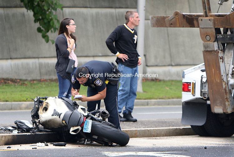 WATERBURY CT. 15 August 2017-081517SV05-A police officer checks information on a motorcycle that was involved in a crash on Hamilton Avenue in Waterbury Tuesday.<br /> Steven Valenti Republican-American