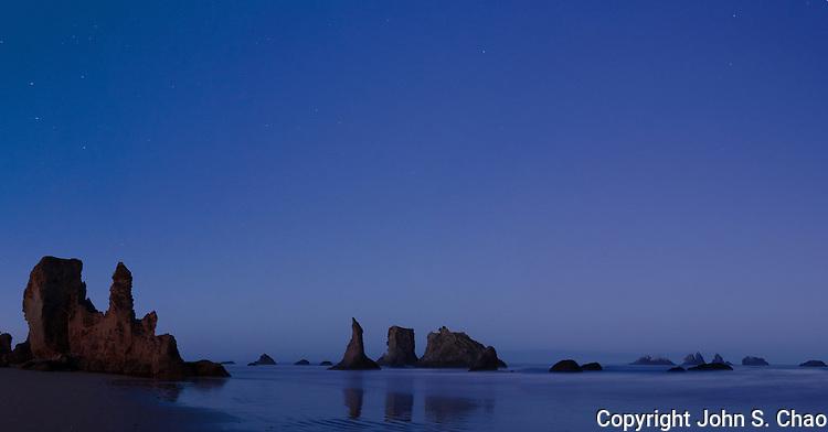 Bandon,Oregon beach sea stacks silhouetted along the Oregon Coast at twilight.