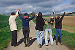 ADFTH1 Back view of three generations extended family raising hands on country walk
