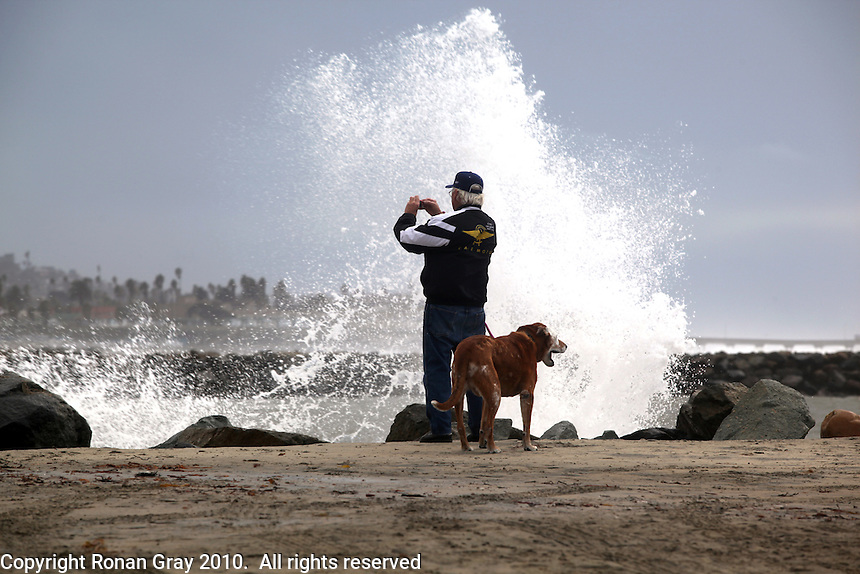 Thursday, Jan 21, 2010:  Jack Underwood of San Diego stops to take a photo while walking his dog Hobbs near the Mission Beach jetty.  WInter storms battered Southern California for a fourth day in a row, bringing strong wind, high surf and rain that caused flooding in many parts of San Diego.