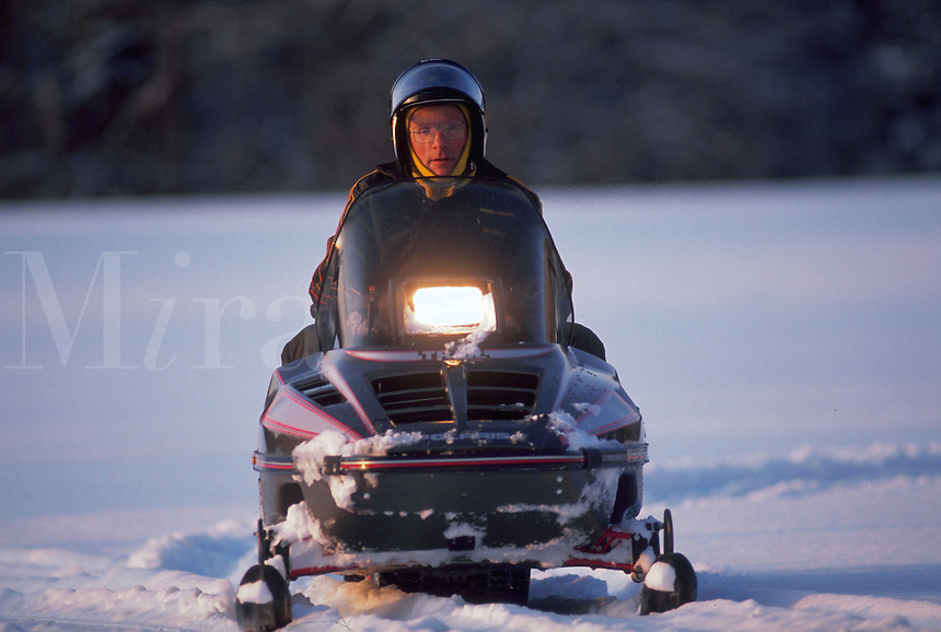 A snowmobiler at dusk.