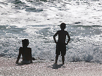 A young boy and girl in the surf on the beach in Swakopmund, Namibia