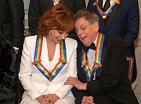 Reba McEntire, left, and Philip Glass two of the recipients of the 41st Annual Kennedy Center Honors, converse as they pose for a group photo following a dinner hosted by United States Deputy Secretary of State John J. Sullivan in their honor at the US Department of State in Washington, D.C. on Saturday, December 1, 2018.  The 2018 honorees are: singer and actress Cher; composer and pianist Philip Glass; Country music entertainer Reba McEntire; and jazz saxophonist and composer Wayne Shorter. This year, the co-creators of Hamilton, writer and actor Lin-Manuel Miranda; director Thomas Kail; choreographer Andy Blankenbuehler; and music director Alex Lacamoire will receive a unique Kennedy Center Honors as trailblazing creators of a transformative work that defies category.<br /> CAP/MPI/RS<br /> &copy;RS/MPI/Capital Pictures