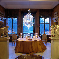 In this dining room a large chandelier hangs over a table displaying a collection of lanterns and candlesticks