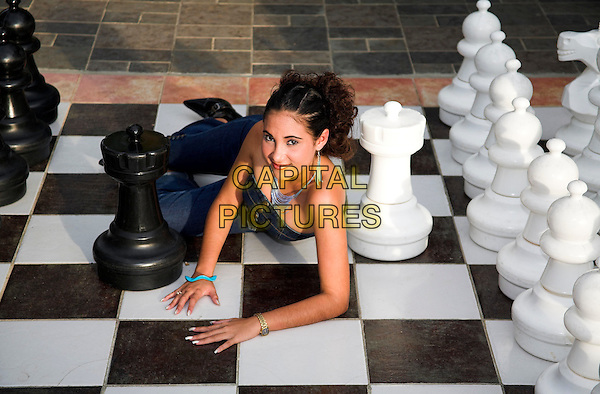 Young lady posing on a large outdoor chessboard, near Trinidad, Cuba