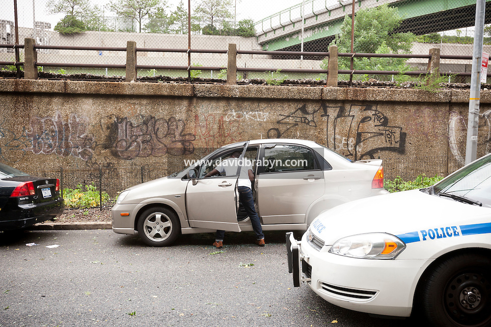 A car owner cleans up his vehicule that was broken into during the night on 12th Avenue in Hamilton Heights, New York City, NY, USA as tropical storm Irene was hitting the region, 28 August 2011. Two other vehicules parked nearby had a smashed window.