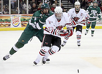 UNO's Eric Olimb races to beat Bemidji State's Drew Fisher to the puck. UNO and Bemidji State skated to a 2-2 tie Friday night at Qwest Center Omaha. (Photo by Michelle Bishop)