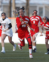 Boston University midfielder Kristen Mogavero (26) brings the ball forward. .Boston College (white) defeated Boston University (red), 12-9, on the Newton Campus Lacrosse Field at Boston College, on March 20, 2013.
