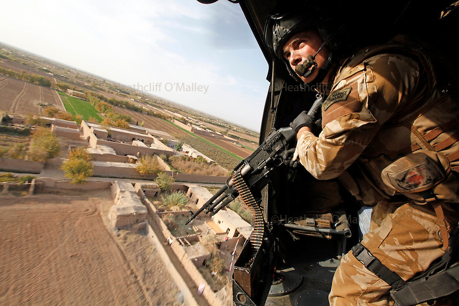 Mcc0018106 . SundayTelegraph..A Marine door gunner on a SeaKing helicopter bound for FOB Shawqat in the Nad e'Ali district of Helmand Province...Afghanistan 7 November 09