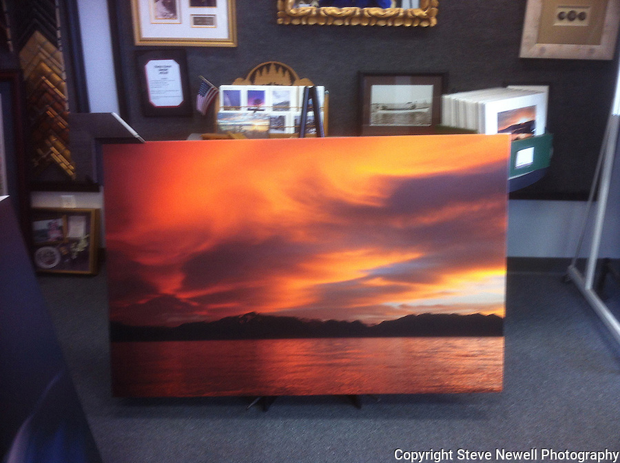 """Fire on the Mountain"" Nevada Beach is located near the casinos on the Nevada side of South Lake Tahoe. This is a photo of one of my giclee prints on canvas at the frame shop. I specialize in large oversize landscapes. The color that developed that night was simply amazing. I shot over 60 photos of this sunset. The clouds started out white and grey then slowly turned the orange shades you see here.  Out of the 60 photos I took of this sunset only 3 have this shape and color.  Sunsets are extremely difficult to capture due to the changing light available and short amount of time to capture it. Mt Tallac can be seen across the water with its identifiable cross. This sunset truly reminded me of a Fire on the Mountain!!"