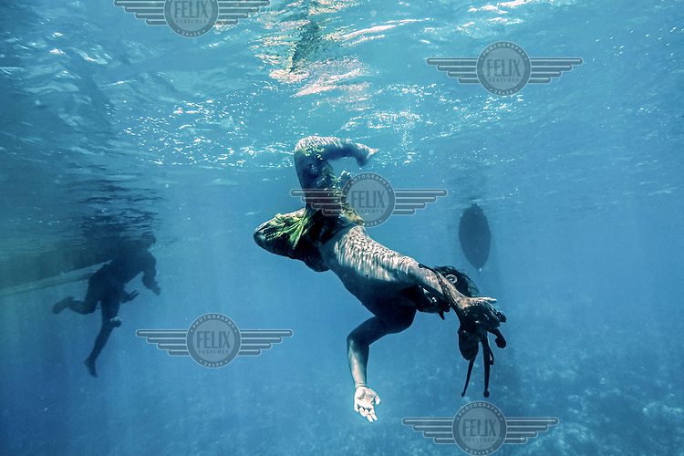 Marjono Lessing (35) dangles an octopus lure in the sea off Kabalutan. Octopus is one of the main sources of income for the Bajau.