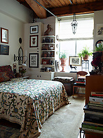 The bedroom's crewel bedspread was bought in a thrift shop, the English tufted-leather chest was found on 1stdibs, and the French lantern is from David Stypmann Co.; the rug is from J&D Oriental Rugs, and the walls are painted in Donald Kaufman Color's DKC-43.