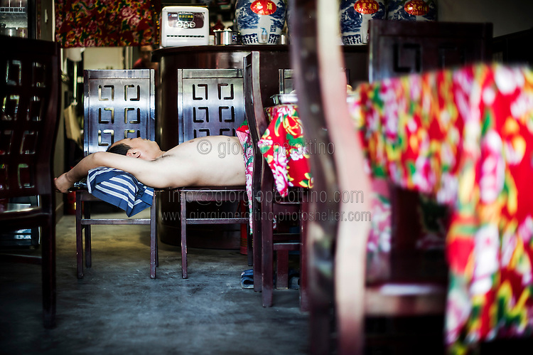 """A Chinese man takes a rest on a chair in his restaurant in PingYao, China, July 30, 2014. <br /> <br /> This image is part of the series """"24/7"""", an ironic view on restless and fast-growing Chinese economy described through street vendors and workers sleeping during their commercial daily activity. <br /> <br /> © Giorgio Perottino"""