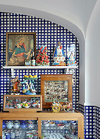 The walls of the kitchen are lined with blue and white checked tiles against which is displayed an array of religious icons and other objects