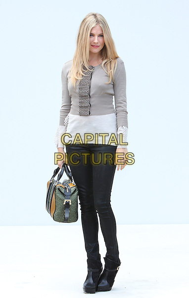 Sienna Miller.Burberry Prorsum S/S Show Arrivals at Kensington Gardens, London, England..September 19th 2011.LFW full length black skinny jeans denim white beige grey gray top green bag purse platform shoes .CAP/ROS.©Steve Ross/Capital Pictures