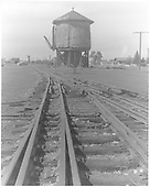 View of Antonito water tank with complicated third rail trackwork in foreground.<br /> D&amp;RGW  Antonito, CO  Taken by Morse, Ron - 3/2/1964