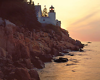 Sunrise glow on the Bass Harbor Lighthouse and a lobster boat; Acadia  National Park, ME