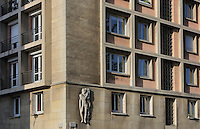 Detail of the facade of an apartment block on the corner of Avenue Foch and Rue Sery, designed by Auguste Perret, 1874-1954, who led the reconstruction of Le Havre in the 1950s, after the town was completely destroyed in WWII, Le Havre, Normandy, France. The relief sculpture, 1953, is by Jean-Marie Baumel and his wife Marthe Schwenck, and shows a man in classical style playing a lyre representing Music, with inscribed names of artists, Andre Caplet, Pierre Beauvalet, Pierre Maumont and Henry Woollett. Avenue Foch is one of the widest avenues in Europe and forms part of the 'Monumental Triangle' at the heart of Le Havre's reconstruction plans. The centre of Le Havre is listed as a UNESCO World Heritage Site. Picture by Manuel Cohen