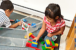 Education preschool 3 year olds boy and girl playing separately near to each other girl with colored plastic Duplo bricks  boy with train set horizontal