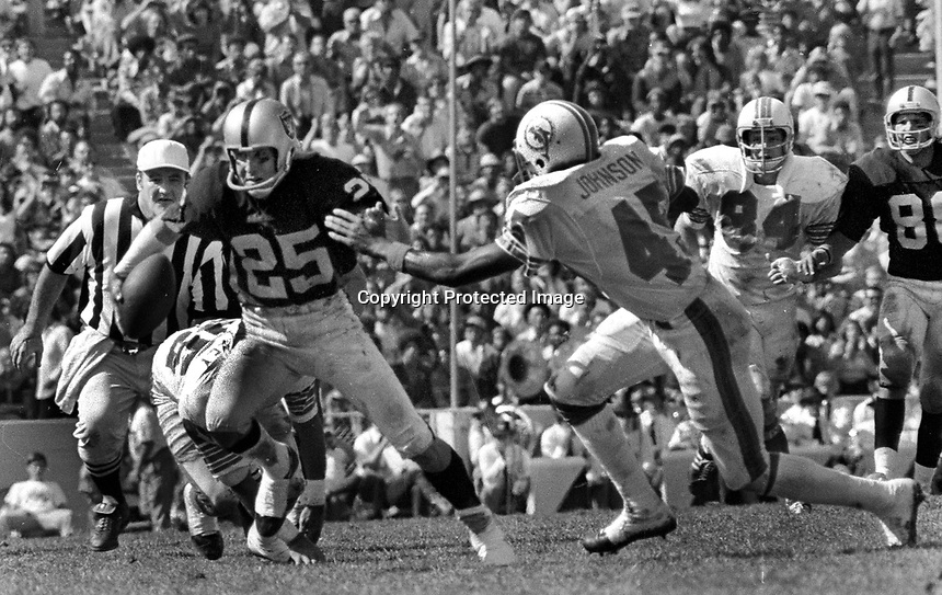 Raiders Fred Biletnikoff runs away from Miami's Curtis Johnson..Raiders defeated the Dolphins 12-8 to snap Miami's NFL record win streak at 18 games in a row.<br /> (1973 photo/Ron Riesterer)
