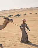 OMAN, Wahiba Sands, teenage boy leading camel in Wahiba Sands
