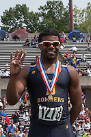 John Burroughs senior Ezekiel Elliott stands atop the awards podium and holds up four fingers for the four state titles he won in 2 hours and 35 minutes at the 2013 Missouri High School State Track and Field Championships. Elliott claimed the 110-meter hurdles, 100-meter dash, 300-meter hurdles, and 200-meter dash, earning 40 team points of the Bombers 55.5 points for second-place, just 2.5 points behind champion Grandview. The performance and season Elliott had earned him the Gatorade Missouri Track and Field Athlete of the Year honor.