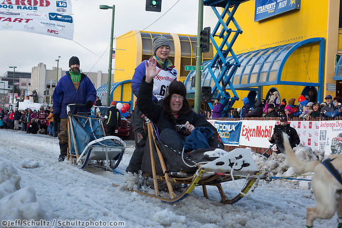 Yuka Honda and team leave the ceremonial start line with an Iditarider at 4th Avenue and D street in downtown Anchorage, Alaska during the 2015 Iditarod race. Photo by Jim Kohl/IditarodPhotos.com
