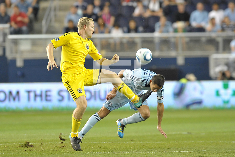 Kevin Burns (yellow) Columbus Crew clears the ball from  Davy Arnaud Sporting KC... Sporting Kansas City defeated Columbus Crew 2-1 at LIVESTRONG Sporting Park, Kansas City, Kansas.