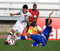 Esteban Rodriguez (8) of the United States is tackled by Kevin Barahona (16) of El Salvador during the quarterfinals of the CONCACAF Men's Under 17 Championship at Catherine Hall Stadium in Montego Bay, Jamaica. The USA defeated El Salvador, 3-2, in overtime.