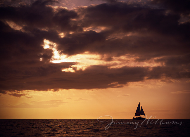 A sailboat sails at sunset through the Pacific Ocean off the coast of Hawaii