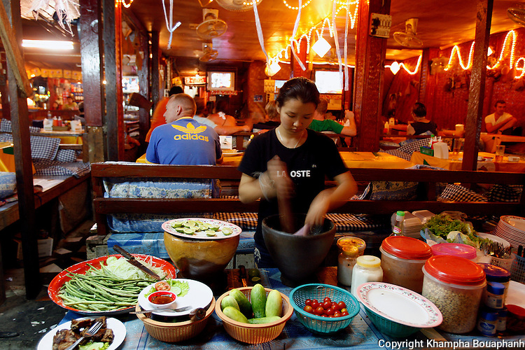 A vendor cooks for guest in Vang Vieng, Laos on Tuesday, March 4, 2008.  A small town with its airfield where America America's plane used during the Vietnam War, Vang Vieng is a popular stop for backpackers.  (Star-Telegram/Khampha Bouaphanh).**NO SALES, NO MAGS**