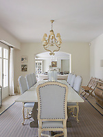 Cool contemporary tones of blue and cream have been used in the dining room to coordinate with the living room beyond