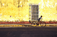A boy rides his bike by the colorful weathered facad of a building in Tlacotalpan. The colonial port of Tlacotalpan is one of the best preserved small cities in mexico, it has been declared a World Heritage town.  It is also the epicenter of the Cuban-Spanish influenced  Son Jarocho music.
