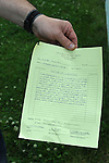 Mikhail Mazo, 52, a Russian immigrant, holds up the warning notice he received for not trimming his lawn from the suburban Chicago municipality of Buffalo Grove, Illinois on July 2, 2009.