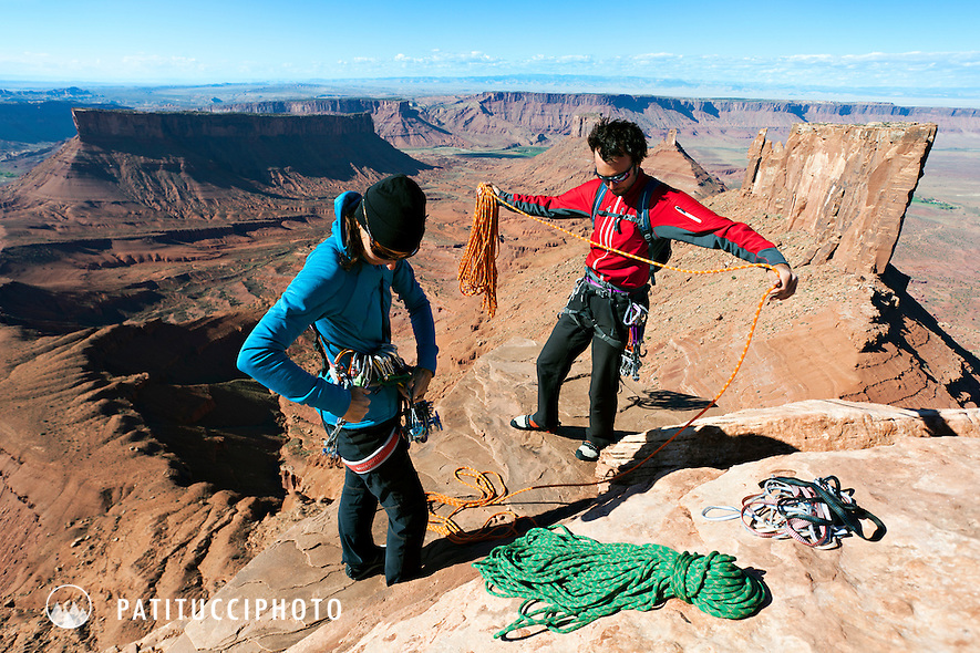 Two climbers on top of Castleton Tower, coiling rope and getting ready to rappel. Castle Valley, Utah