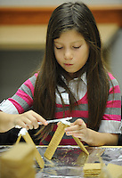 STAFF PHOTO ANDY SHUPE - Daniela Vicari, 9, of Springdale concentrates while making a gingerbread house Saturday, Dec. 20, 2014, at the Springdale Public Library. Children made houses out of graham crackers and decorated them with candy and icing.