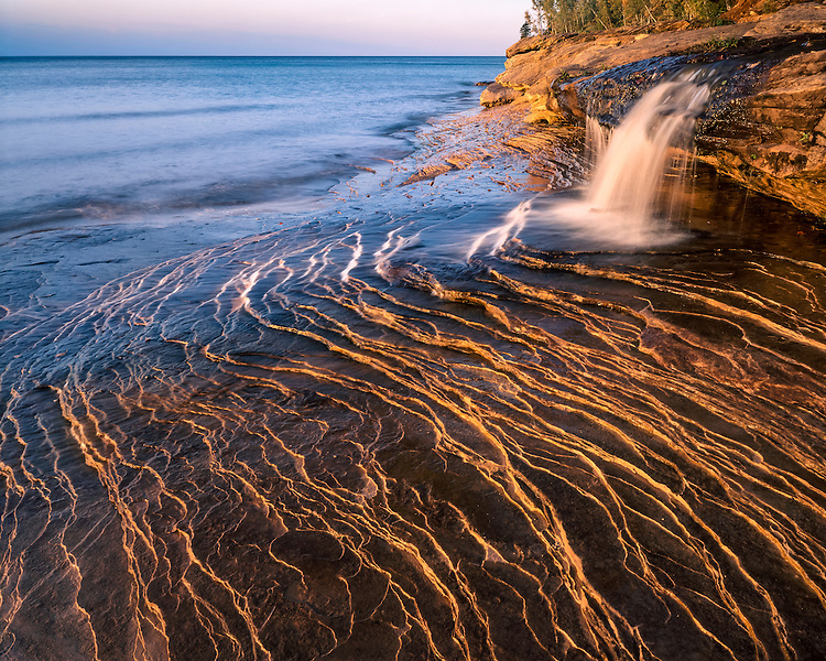 Sunset light on a waterfall and the eroded shore of Lake Superior at Miners Beach; Pictured Rocks National Lakeshore, MI