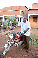 N. Uganda, Kitgum District. Peter C. Alderman Foundation project. Local PCAF staff: Michael Okech(Kitgum psychiatric staff) with his motorcycle.