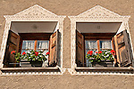 Windows in the small town of Promotogno, a Swiss town in the Bregaglia Valley. The decorations on the house are patterns scratched out of the still wet wall, decorative artwork called sgraffiti, traditionally done in two colors and originating in Italy, brought to the Engadin region of Switzerland in the 16th century and is still used today