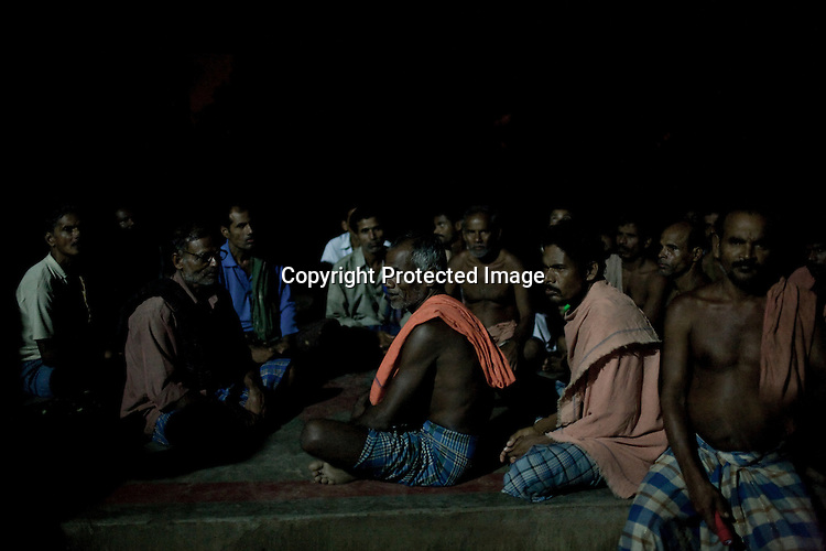 """Villagers meet after dusk to take account of the day and discuss their strategy on how to tackle the problem of land acquisition by Posco. many villagers take on the responsibility to guard the gate leading to their village Dingkhia in Orissa, India. These villagers have formed an agitating group, """"Posco Pratirdh Sangram Samiti"""" to oppose the construction of Posco port in their village."""
