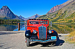 The Glacier1936  Red Bus Touring vehicle sits in front of the lake at Glacier National Park in Montana, USA>