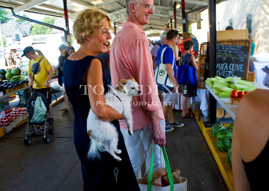 """Ann Arborites Kristi and Johannes Vanderhyde, and their dog """"Petey"""", browse the Farmer's Market, Saturday, Sept. 3, 2011 in Ann Arbor, Mich. (Tony Ding for The New York Times)"""