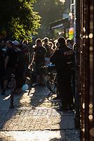 Am Pfingstsonntag den 20. Mai 2018, wurden in Berlin mehrere Haeuser besetzt. Mit dieser Aktion wollten die Besetzer ein Zeichen gegen Verdraengung und Wohnungsnot setzen. Um 21 Uhr raeumte die Polizei zeitgleich in den Bezirken Kreuzberg und Neukoelln die Besetzungen, nachdem auf Druck des Senat die landeseigenen und privaten Eigentuemer Strafantrag und ein schriftliches Raeumungsbegehren gestellt hatten.<br /> Im Bezirk Kreuzberg wurde in der Reichenbergerstrasse 114 ein seit vielen Jahren leer stehender Ladenraum besetzt. Die Besetzer wollten in den Raeumen einen Stadtteilladen einrichten. Bei der Raeumung wurden mehrere Personen durch Tritte und Schlaege von Polizeibeamten und durch den Einsatz von Pfefferspray verletzt.<br /> Besitzer der Reichenbergerstrasse 114 ist die , der Akelius GmbH.<br /> Im Bild: Ein Polizeibeamter beobachtet die Menschen vor dem besetzten Ladenraum.<br /> 20.5.2018, Berlin<br /> Copyright: Christian-Ditsch.de<br /> [Inhaltsveraendernde Manipulation des Fotos nur nach ausdruecklicher Genehmigung des Fotografen. Vereinbarungen ueber Abtretung von Persoenlichkeitsrechten/Model Release der abgebildeten Person/Personen liegen nicht vor. NO MODEL RELEASE! Nur fuer Redaktionelle Zwecke. Don't publish without copyright Christian-Ditsch.de, Veroeffentlichung nur mit Fotografennennung, sowie gegen Honorar, MwSt. und Beleg. Konto: I N G - D i B a, IBAN DE58500105175400192269, BIC INGDDEFFXXX, Kontakt: post@christian-ditsch.de<br /> Bei der Bearbeitung der Dateiinformationen darf die Urheberkennzeichnung in den EXIF- und  IPTC-Daten nicht entfernt werden, diese sind in digitalen Medien nach §95c UrhG rechtlich geschuetzt. Der Urhebervermerk wird gemaess §13 UrhG verlangt.]
