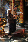 Bao-jhong Yi-min Temple, Kaohsiung -- Taoist worshipers in prayer at a temple.