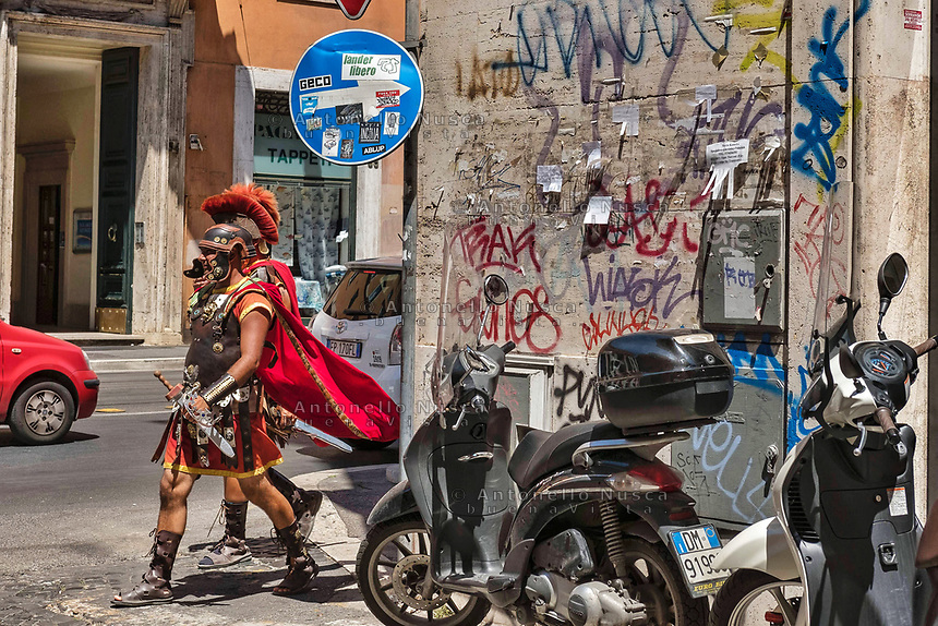 Rome, Italy, June 21, 2017. Due uomini vestiti da centurioni camminano in una strada degradata del centro storico. Two men dressed as Roman centurions walk in the centre of Rome.<br /> Ad un anno dalla elezione a sindaco di Roma di Virginia Raggi, la condizione di degrado non accenna a migliorare.<br /> One year after the election as mayor of the candidate of M5S party, Rome is worsening day by day.