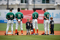 Greensboro Grasshoppers J.C. Millan (14), Marcos Rivera (11), Jose Devers (2), and Micah Brown (10) stand for the national anthem with local little leaguers before a game against the Lakewood BlueClaws on June 10, 2018 at First National Bank Field in Greensboro, North Carolina.  Lakewood defeated Greensboro 2-0.  (Mike Janes/Four Seam Images)
